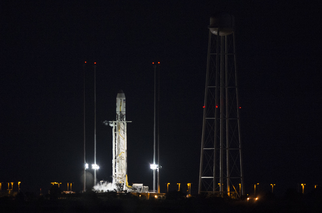 This image provided by NASA shows the Orbital Sciences Corporation Antares rocket, with the Cygnus spacecraft onboard, on launch Pad-0A after the launch attempt was scrubbed because of a boat down ...