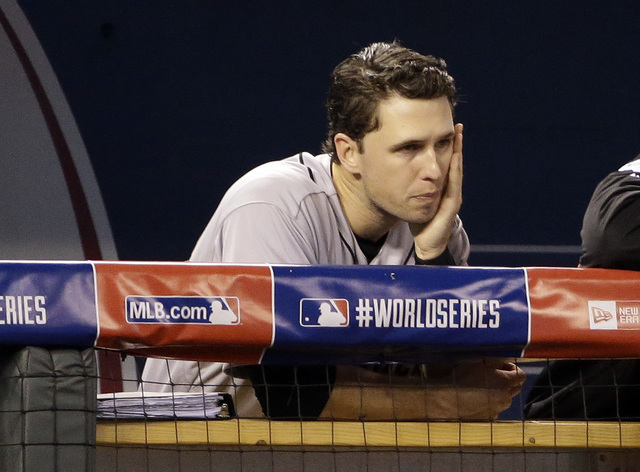 San Francisco Giants' Buster Posey watches from the dugout during the second inning of Game 6 of baseball's World Series against the Kansas City Royals Tuesday, Oct. 28, 2014, in Kansas City, Mo.  ...