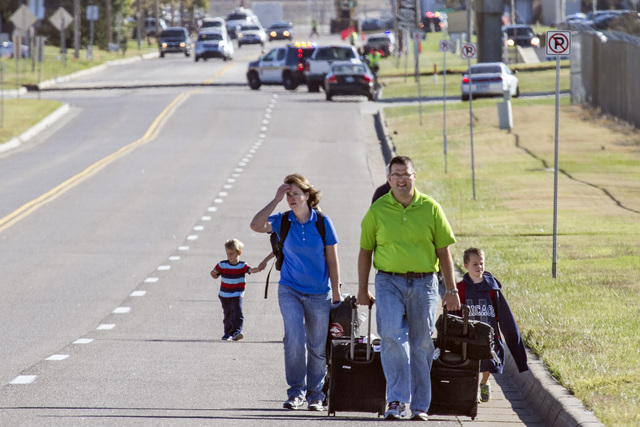 Scott Gatzulis and his family, returning to Wichita from a Hawaii vacation, walk to their car at Mid-Continent Airport in Wichita, Kansas, Thursday, Oct. 30, 2014, after a small plane crashed into ...