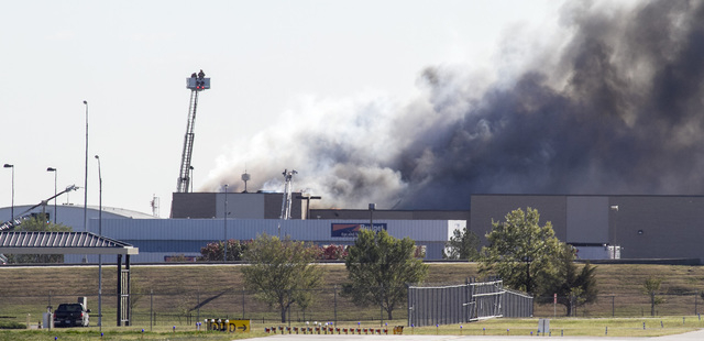 Firefighters try to put out a fire in a building near Mid-Continent Airport in Wichita, Kansas, Thursday, Oct. 30, 2014, shortly after a small plane crashed into the building, killing several peop ...