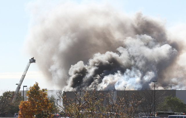 Smoke billows from a building at Mid-Continent Airport in Wichita, Kansas, Thursday. Oct. 30, 2014, shortly after a small plane crashed into the building, killing several people including the pilo ...