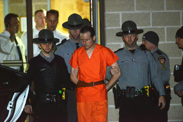 State troopers escort Eric Matthew Frein from the Blooming Grove barracks early Friday, Oct. 31, 2014. Frein, accused of opening fire on the barracks Sept. 12, killing state police Cpl. Bryon K. D ...