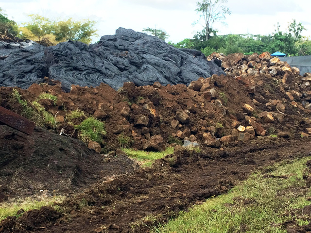 This Oct. 30, 2014 photo from the U.S. Geological Survey shows where lava flow has come into contact and inflated against an artificial berm, to a level much higher than that of the berm, on priva ...