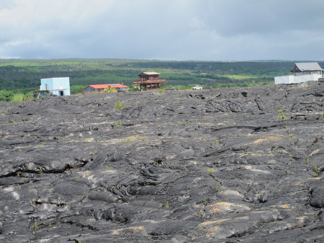 Houses sit among recent lava flow in Kalapana, Hawaii on Thursday, Oct. 30, 2014. Ten miles from Pahoa, the small Hawaii town held hostage by a slowly oozing stream of lava from Kilauea volcano, p ...