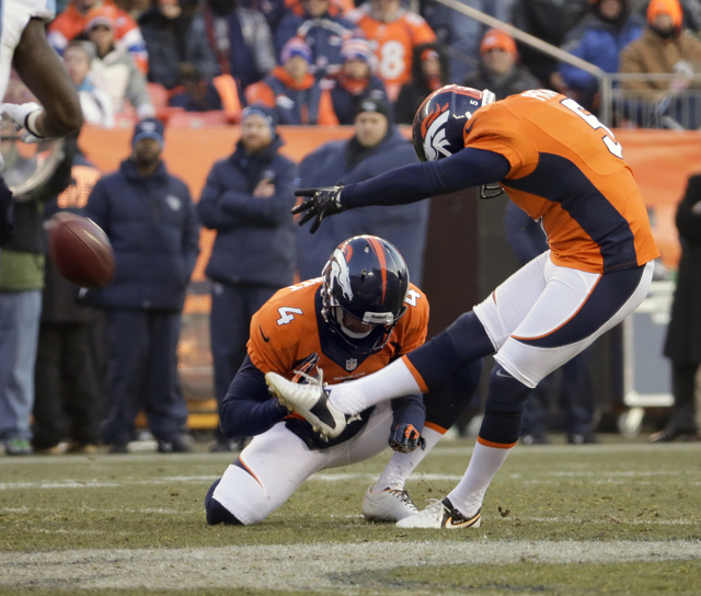 Denver Broncos kicker Matt Prater, right, kicks a 64-yard field goal as Britton Colquitt holds during the first half of an NFL football game against the Tennessee Titans on Sunday, Dec. 8, 2013, i ...