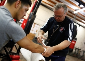 """Trainer and gym owner Pat Barry, right, tapes the hands of Diego Magdaleno before training for his fight against WBO super featherweight champion Roman """"Rocky"""" Martinez at Barry's Boxing Center ..."""