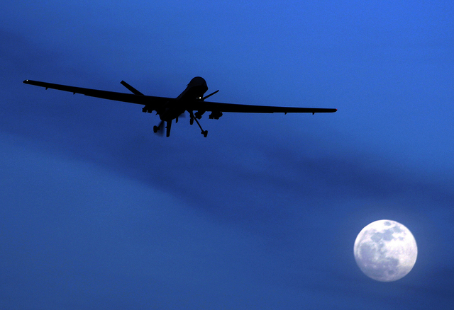 An unmanned U.S. Predator drone flies over Kandahar Air Field in southern Afghanistan in late January. (AP Photo/Kirsty Wigglesworth, file)