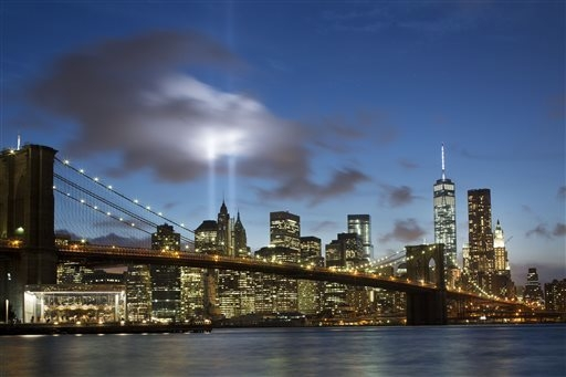 The Tribute in Light rises behind the Brooklyn Bridge and buildings adjacent to the World Trade Center complex in New York. The tribute, an art installation of 88 searchlights aiming skyward in tw ...