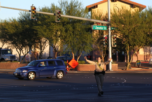 Las Vegas police officers direct traffic after an accident shut down the power, affecting the traffic lights, at the intersection of Charleston and Decatur boulevards in Las Vegas on Tuesday, Oct. ...