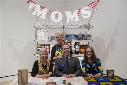 This September 2014 photo provided by Crystal Bridges Museum of American Art shows artist Andy Ducett with his mom Marilyn behind him and two volunteers at the Mom Booth at the museum in Bentonvil ...