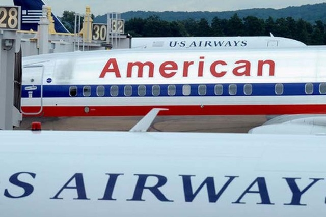 An American Airlines plane is shown between two US Airways planes at Washington's Ronald Reagan National Airport. The two airlines will combine their frequent flier programs early next year(AP Pho ...