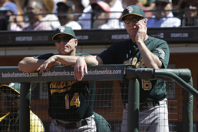 Oakland Athletics bench coach Chip Hale (14) and manager Bob Melvin (6) watch from the dugout during a baseball game against the San Francisco Giants in San Francisco, Thursday, May 30, 2013. The  ...