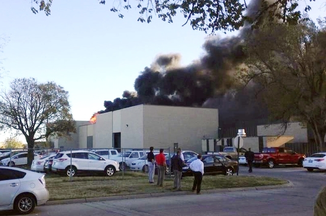 Black smoke billows from a building at Mid-Continent Airport where officials say a plane crashed Thursday, Oct. 30, 2014, in Wichita, Kansas. (AP Photo/KAKE News)