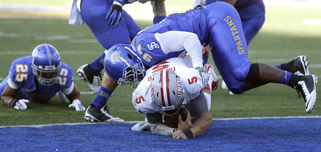 UNLV's Blake Decker (5) scores a touchdown beneath the tackle of San Jose State's Eugene Taylor during the first half of an NCAA college football game Saturday, Oct. 4, 2014, in San Jose, Calif. ( ...
