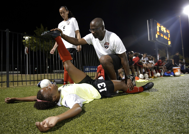 Trinidad & Tobago trainer Michael Taylor, center, helps Danielle Blair (13) stretch at half time as Arin King (5) talks with Blair during an exhibition soccer scrimmage against FC Dallas' U-18 wom ...