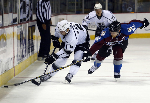 Colorado Avalanche left wing Gabriel Landeskog (92) reaches in to steal the puck from Los Angeles Kings defenseman Jake Muzzin (6) during the first period of a preseason NHL hockey game Thursday,  ...