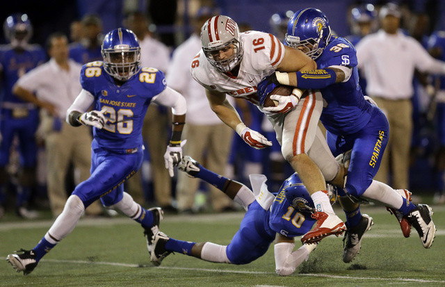 UNLV's Taylor Barnhill (16) is tackled by San Jose State's Maurice McKnight (10) and Vince Buhagiar (36) during the second half of an NCAA college football game Saturday, Oct. 4, 2014, in San Jose ...