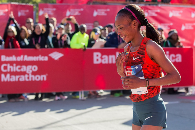 In this Sunday, Oct. 12, 2014 file photo, Rita Jeptoo of Kenya reacts after crossing the finish line to win the women's race during the Chicago Marathon, in Chicago, Illinois. The agent for Chicag ...