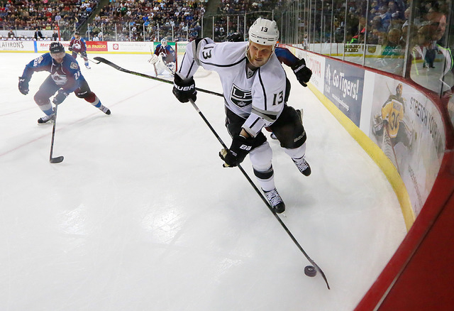 Los Angeles Kings left wing Kyle Clifford (13) moves the puck out of the corner against the Colorado Avalanche during the second period of a preseason NHL hockey game Thursday, Oct. 2, 2014, in Co ...