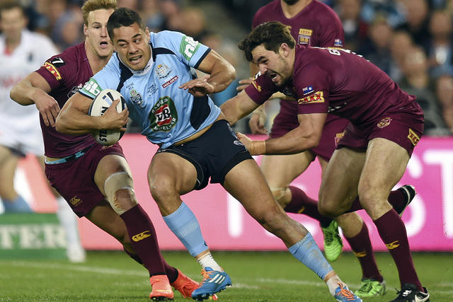 In this June 18, 2014 photo, Jarryd Hayne, center, escapes a tackle during a State of Origin rugby league series game in Sydney, Australia. Hayne stunned the rugby league world by quitting his lon ...