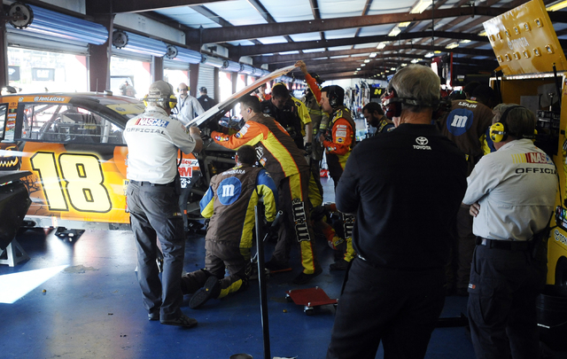 Crew members work on Kyle Busch's wrecked car during the NASCAR Sprint Cup Series auto race at Talladega Superspeedway Sunday, Oct. 19, 2014, in Talladega, Ala. (AP Photo/Rainier Ehrhardt)