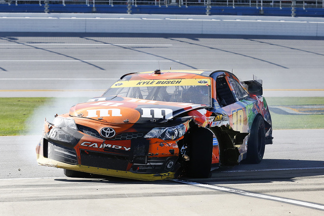 Kyle Busch pulls his damaged car behind the pit wall after crashing during the  NASCAR Sprint Cup Series auto race at Talladega Superspeedway, Sunday, Oct. 19, 2014, in Talladega, Ala. (AP Photo/B ...