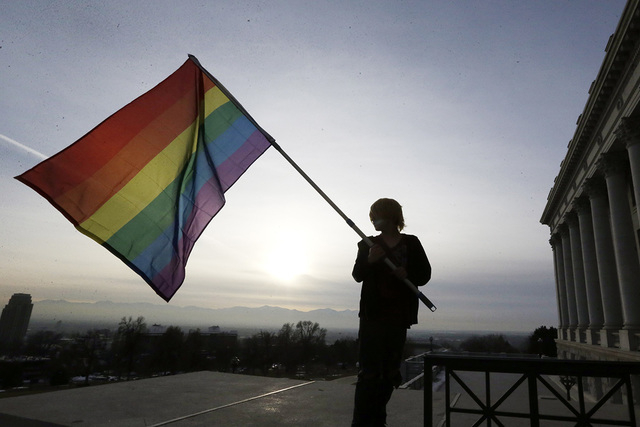 In this Jan. 28, 2014, file photo, Corbin Aoyagi, a supporter of gay marriage, waves a rainbow flag during a rally at the Utah State Capitol in Salt Lake City. The U.S. Supreme Court on Monday, Oc ...