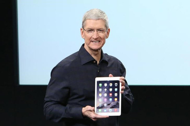 Apple CEO Tim Cook holds an iPad during a presentation at Apple headquarters in Cupertino, California, Thursday, Oct. 16, 2014, when the company introduced a faster, slimmer iPad Air 2. (Reuters/R ...