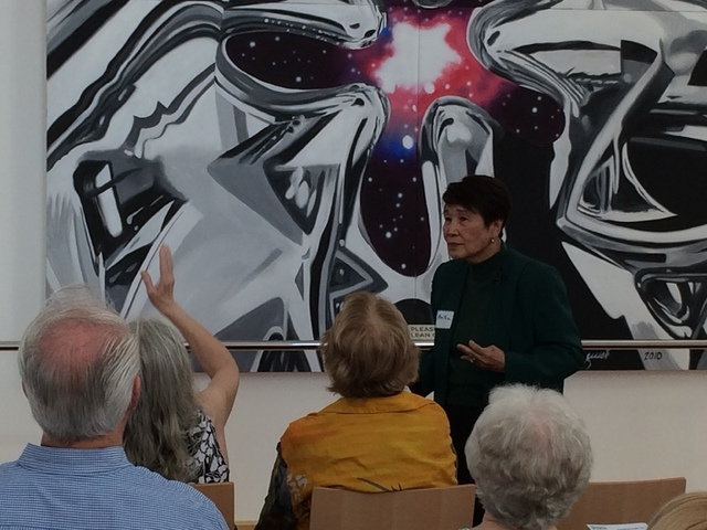 Three-year docent Anita Daus discusses a 20-foot by 10-foot painting by James Rosenquist. (Linda Simpson/View)