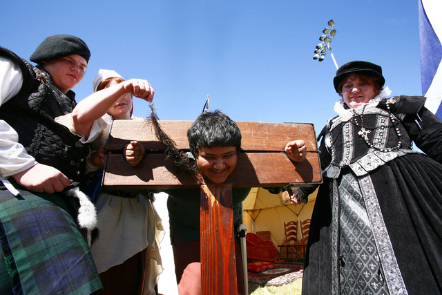 """BC-RENFAIR--With Del Sol High School JuniorSergio Maquez """"detained"""" in the stock, (Left) House of Stuart Paige, William Henson  looks on while Mistress Loghaire applies the feather to to ..."""