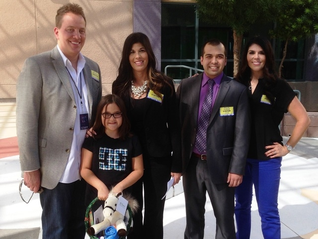 Samantha Diblasi, second from left, third grader at Bilbray Elementary School, poses for a photo with radio hosts Mark DiCiero, from left, and Mercedes Martinez, radio hosts of Mix 94.1, and Wells ...