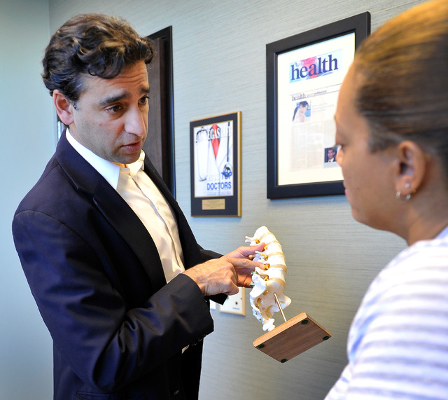 Neurosurgeon and spine specialist Dr. Aury Nagy, left, speaks with staff member Monica Rios posing as a patient at his Las Vegas office on Monday, Sept. 29, 2014. (David Becker/Las Vegas Review-Jo ...