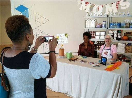 This Sept. 27, 2014 photo shows a visitor posing for a photo with volunteer Louise Lamb, seated right, at the Mom Booth at Crystal Bridges Museum of American Art in Bentonville, Ark. The Mom Booth ...