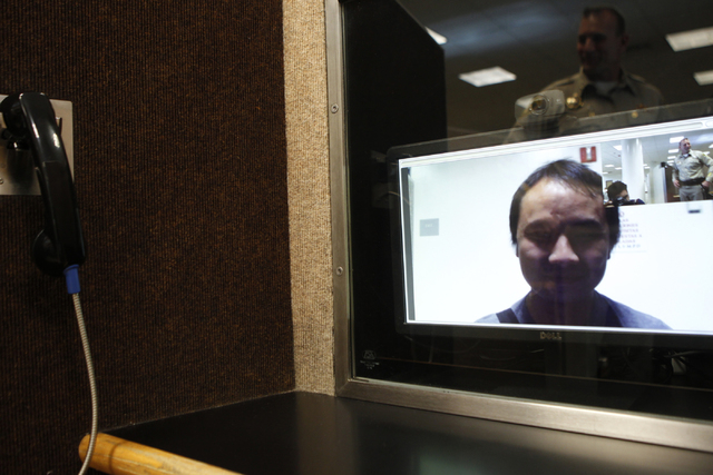 Chris Thao is seen through a video monitor as he demonstrates the video communication system at one of their booths at the Clark County Detention Center visitor lobby in Las Vegas during a tour Fr ...