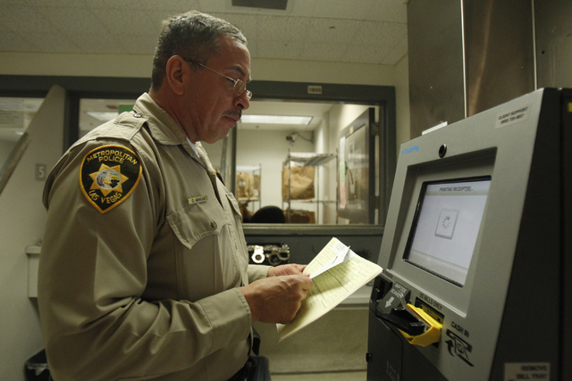 Clark County Detention Center corrections officer David Mancha uses a TouchPay kiosk to record money from a booked detainee in the pre-arrest area at the Clark County Detention Center in Las Vegas ...