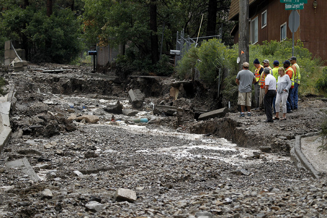 Residents gather near what was Rainbow Canyon Road in the Rainbow Subdivision on Mount Charleston on Monday, July 28, 2014. The road was washed away by flash flooding caused by rainfall on Monday. ...
