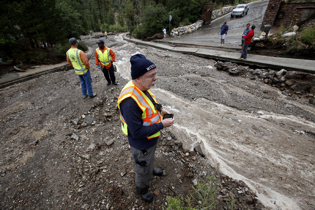 Mike McGroarty, a resident of Rainbow subdivision, stands near what was Rainbow Canyon Road in the Rainbow Subdivision on Mount Charleston on Monday, July 28, 2014. The road was washed away by fla ...