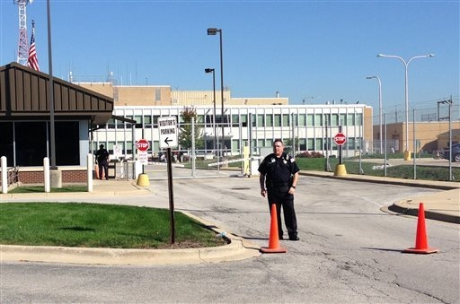 Security stands in front of the air traffic control facility in Aurora, Illinois, on Friday, Sept. 26, 2014, after a fire at the suburban air traffic control facility sent delays and cancellations ...
