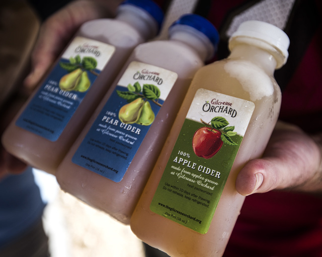 Bill Radcliffe purchases homemade apple cider,right, and pear cider at Gilcrease Orchard, 7800 N. Tenaya Way, on Thursday, Oct. 9, 2014. The ciders are made from apples at the orchard.  (Jeff Sche ...