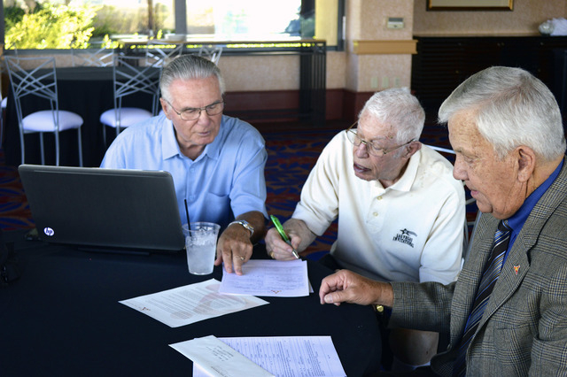 Retiree Bob Brill, center, fills out a form to take part in the Foundation Assisting Seniors' HowRU Program, which calls seniors daily to help ensure their safety. At left is Gary Duffel, vice pre ...