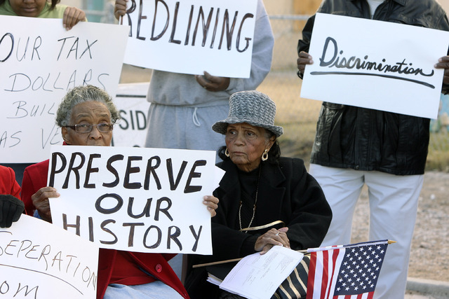 Helen Toland, left, and Sarann Knight-Preddy hold signs as they join other members of their neighborhood during a press conference at the corner of F Street near the Interstate 15 overpass in 2008 ...