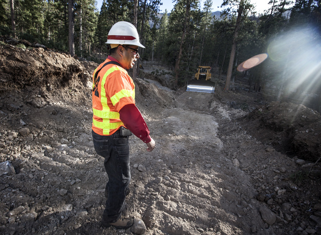 Daniel Calderon with Army Corps of Engineers walks at the site were a berm is being constructed at Rainbow Subdivision in Mount Charleston on Friday, Oct. 10, 2014. The U.S. Forest Service is buil ...