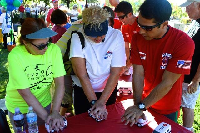 Las Vegas Firefighters teaching residents hands-only CPR at the Summerlin 5K Run and Fun Walk on Saturday, October 11, 2014. (Special to View)
