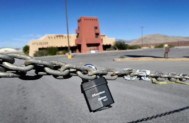 A lock and chain prevents drivers from entering the parking lot in front of the Indian Springs Casino on Tuesday, Oct. 14, 2014. The roadside casino, 45 miles north of downtown Las Vegas, was shut ...