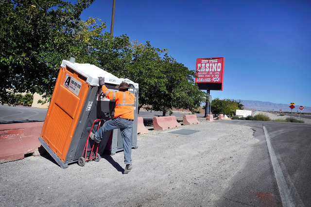 Louis Fuentes loads a portable toilet that was temporarily stored in front of the now closed Indian Springs Casino on Tuesday, Oct. 14, 2014. The roadside casino, 45 miles north of downtown Las Ve ...