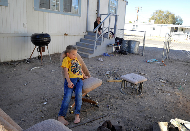 Barrett Colcord, 7, sits in his yard as his mother, Jessica Colcord, watches from her porch in Indian Springs, Nev. on Tuesday, Oct. 14, 2014. The single mother of two, was laid off after the Indi ...