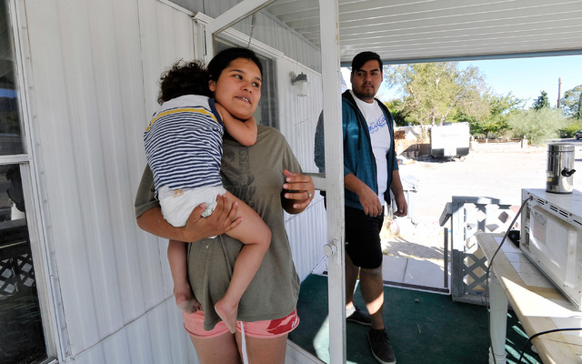 Amanda Ortiz, center, holds her son, two-year-old Jonah Adin, on her porch in Indian Springs, Nev. on Tuesday, Oct. 14, 2014. Ortiz and Cesar Garcia, right, were recently laid off after the Indian ...