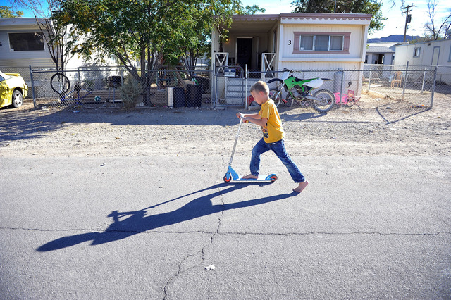Barrett Colcord, 7, scoots along the street in Indian Springs, Nev. on Tuesday, Oct. 14, 2014. Colcord's mother, Jessica Colcord was recently laid off after the Indian Springs Casino closed on Oct ...