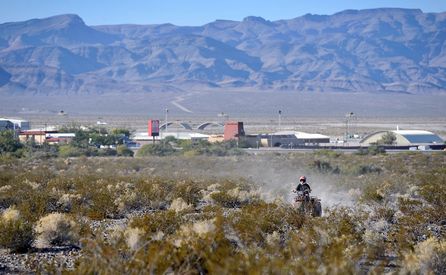 An off-road rider travels along a dirt trail in the desert area in Indian Springs, Nev. on Tuesday, Oct. 14, 2014. The U.S. Government recently completed the purchase of 16.9 acres boarding Creech ...