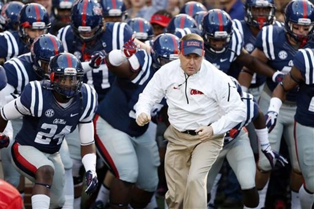 Mississippi football coach Hugh Freeze and his team runs onto the field prior to their game against Tennessee at an NCAA college football game in Oxford, Miss., Saturday, Oct. 18, 2014. (AP Photo/ ...